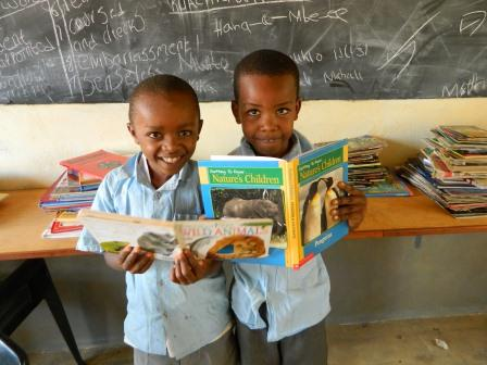 Primary students enjoying new books at Mulundi Community Library, Kitui, Kenya.