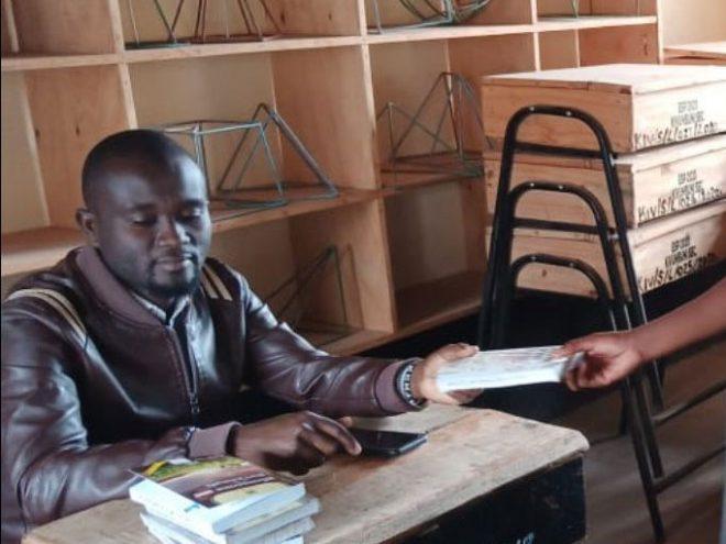 African teacher distributing books to school children